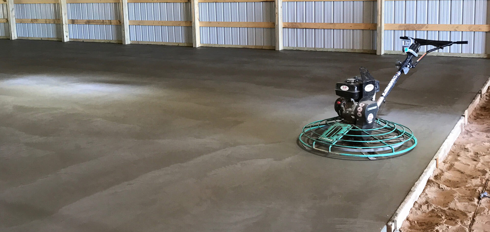 Concrete polisher sitting on a freshly poured concrete floor in a large pole shed