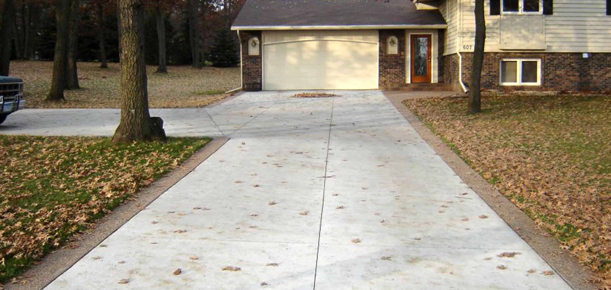 Freshly poured residential concrete driveway with decorative aggregate borders